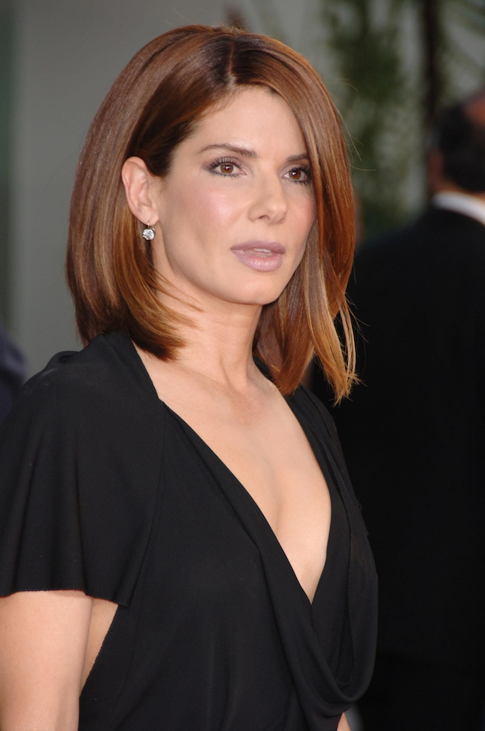 sandra bullock, wearing black dress, layered haircuts with bangs, brown hair side swept, small earrings