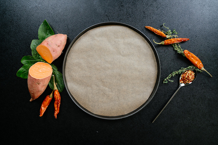 sheet pan, covered with paper, easy dinner recipes, chillis and thyme, sweet potato, cut in half, on black table
