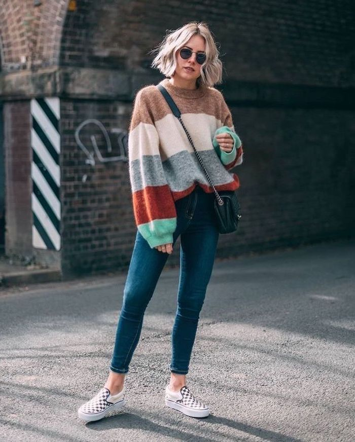 woman standing in the middle of the street, wearing colorful sweater and jeans, layered haircuts with bangs, blonde wavy hair