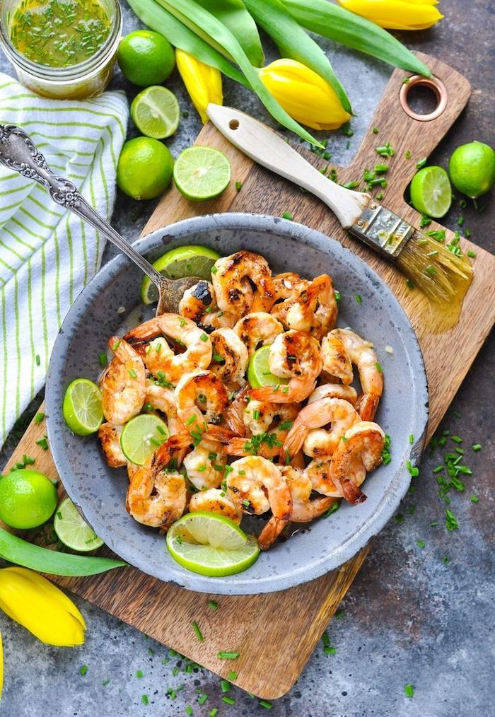 honey lime sauce, shrimp in a ceramic bowl, lime slices inside, low calorie meals, wooden cutting board