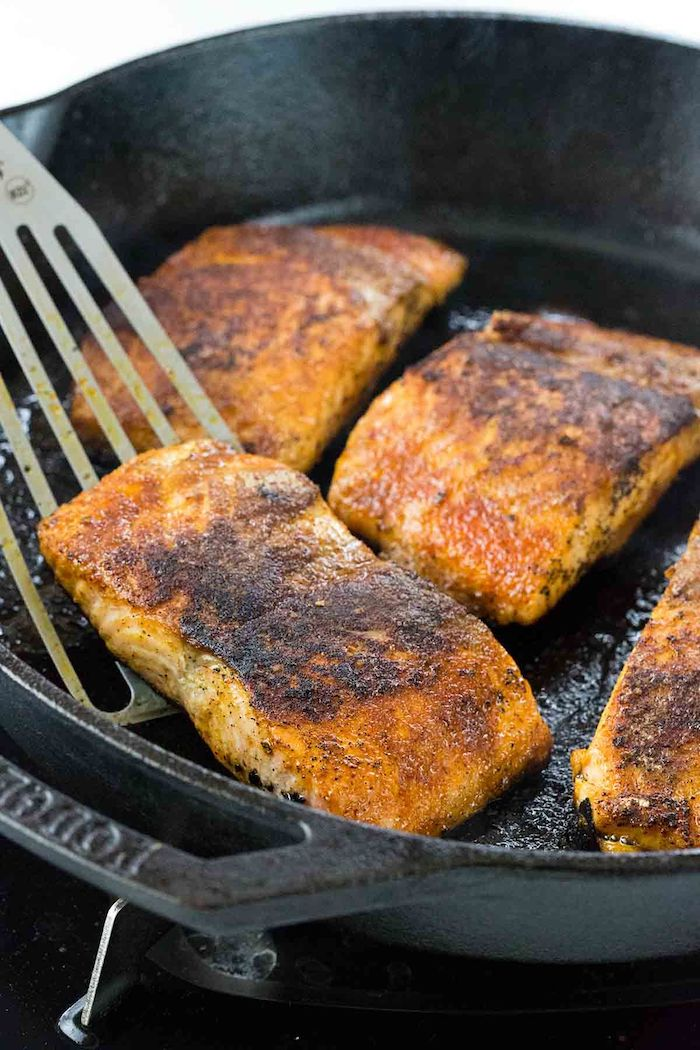 baked salmon, in a black skillet, low calorie meals, metal spatula, white background