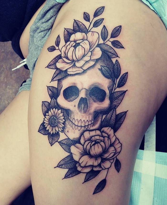 human skull, surrounded by flowers, side thigh tattoo, grey shorts, black t shirt