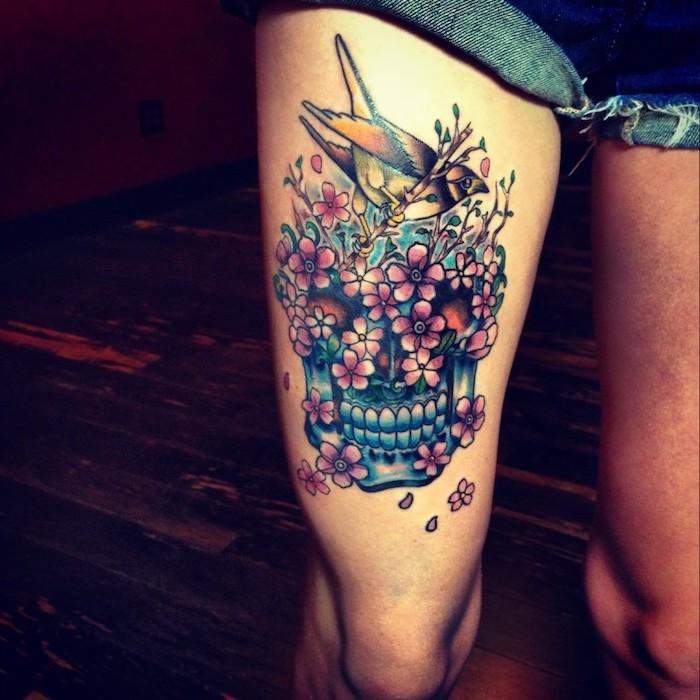 denim shorts, blue skull, pink flowers, hummingbird on top, side thigh tattoo, wooden floor
