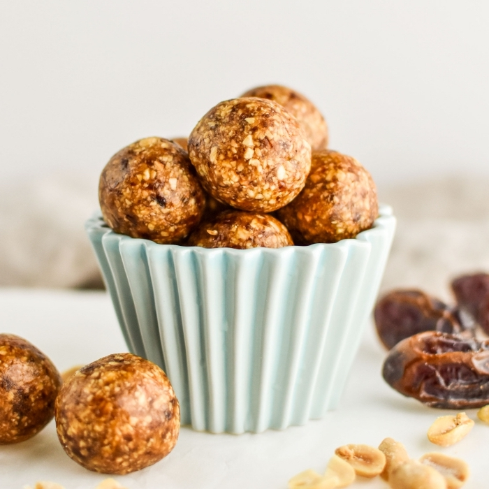 small blue bowl, chocolate peanut butter protein balls, dates and peanuts, scattered on the table