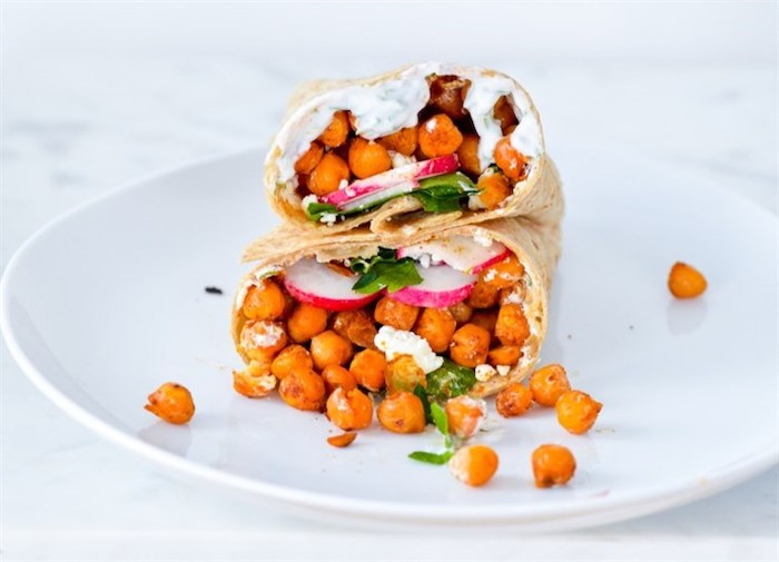 chickpea wrap, with turnip and parsley, yoghurt sauce, sliced in two, on white plate, healthy meal plans