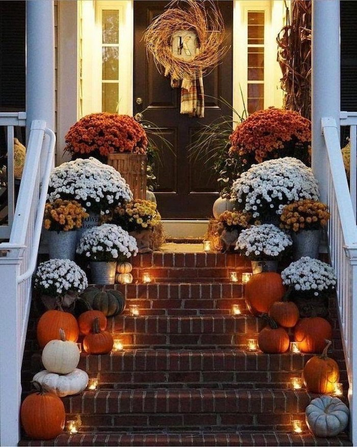 large flower bouquets, pumpkins and candles, arranged on each step, thanksgiving door decor, wreath on the door