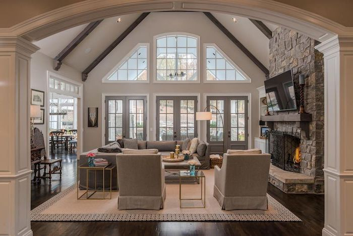 tall ceiling, wooden floor, white carpet, how to vault a ceiling, stone fireplace wall, grey corner sofa, grey armchairs
