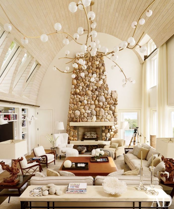 barrel ceiling, wooden ceiling with skylights, stone fireplace wall, vaulted ceiling lighting, hanging chandelier