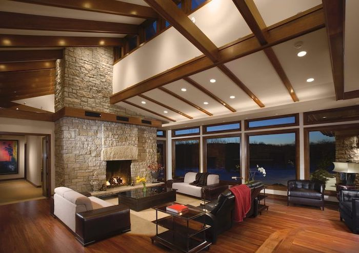 stone fireplace wall, black leather sofa and armchairs, wooden floor, how to vault a ceiling, wooden beams