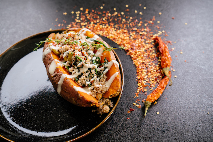 stuffed sweet potato, with sauce and thyme for garnish, in black plate, easy dinner ideas, chilli powder, on black table