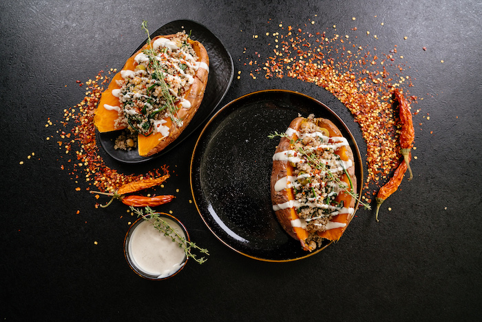 easy dinner recipes, stuffed sweet potatoes, with sauce and thyme for garnish, in black plates, on black table, with chili powder on top