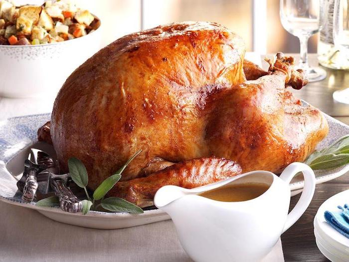 gravy in a jug, roasted turkey, fresh herbs, white plate, how to cook a thanksgiving turkey, thanksgiving dinner