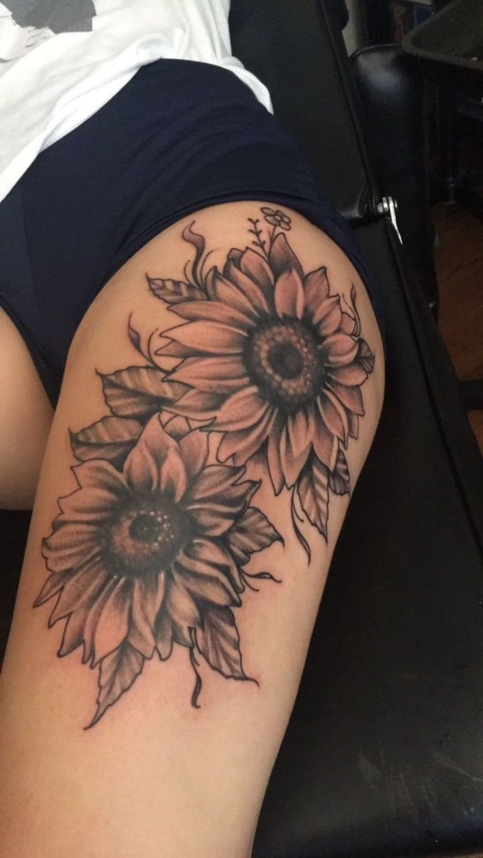two sunflowers, upper thigh tattoo, black shorts, white t shirt, black leather bed