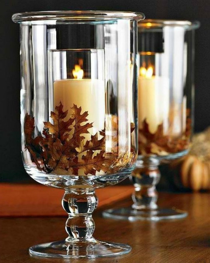 candles in glasses, fall leaves, inside large vases, thanksgiving home decorations, wooden table