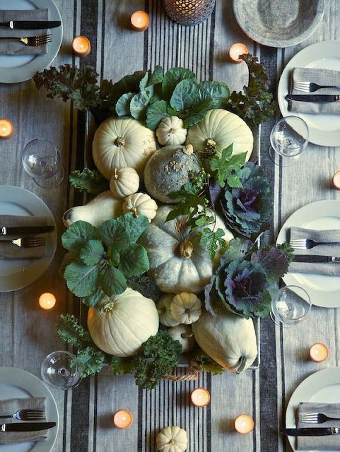 pumpkins and leaves, arranged in the middle of the table, thanksgiving home decorations, plate settings, candles everywhere