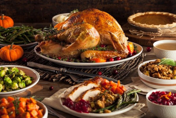 best thanksgiving turkey recipe, roasted turkey, white plate, cranberry sauce, wooden table, different meals