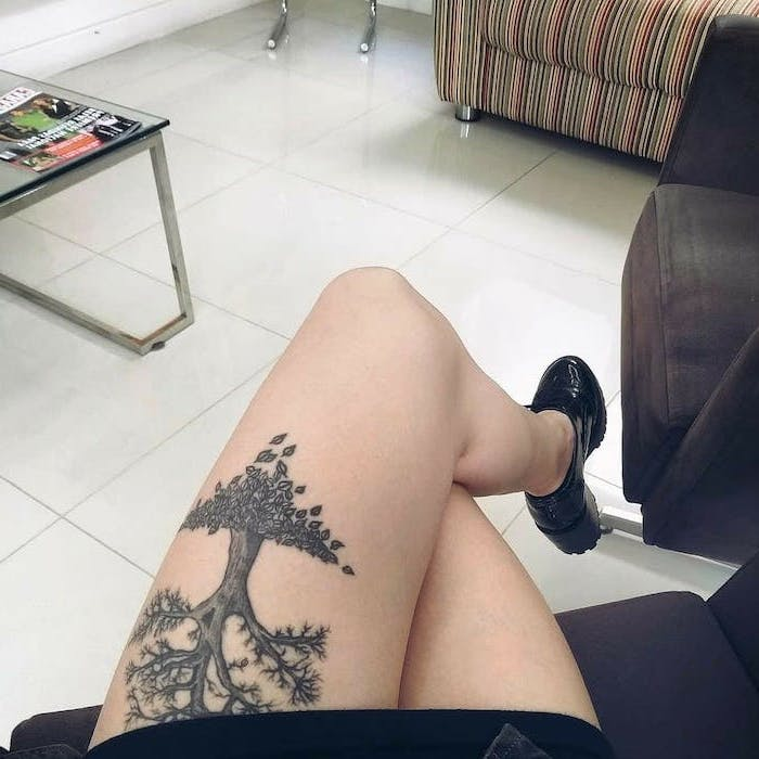 the tree of life, upper thigh tattoo, woman sitting on couch, wearing black shoes, white tiled floor