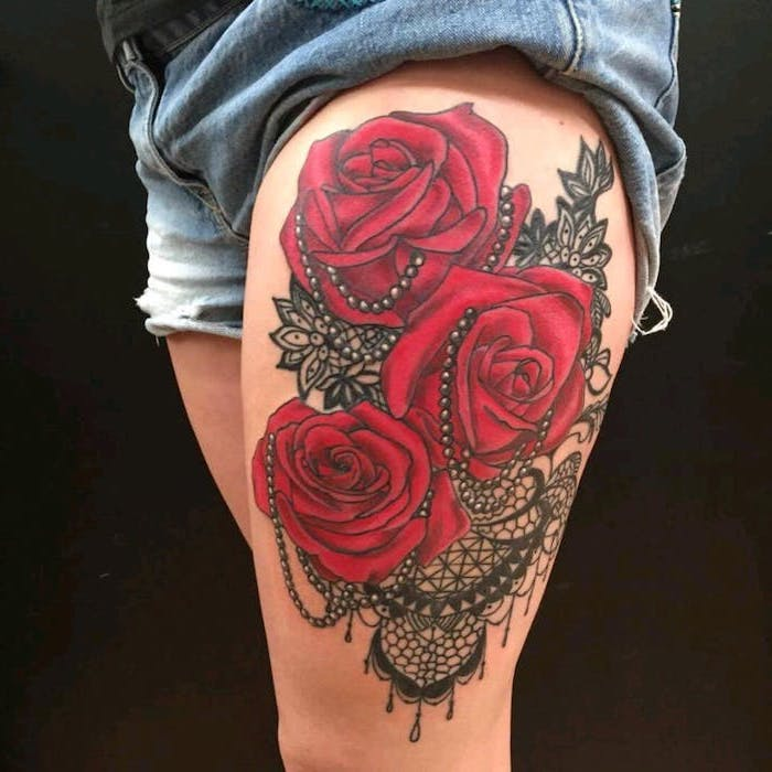 three red roses, black beads, mandala flowers tattoo, denim shorts, black background, lion thigh tattoo