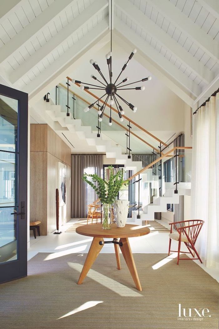vaulted ceiling kitchen, wooden table, entry door, white staircase, hanging chandelier, white curtains