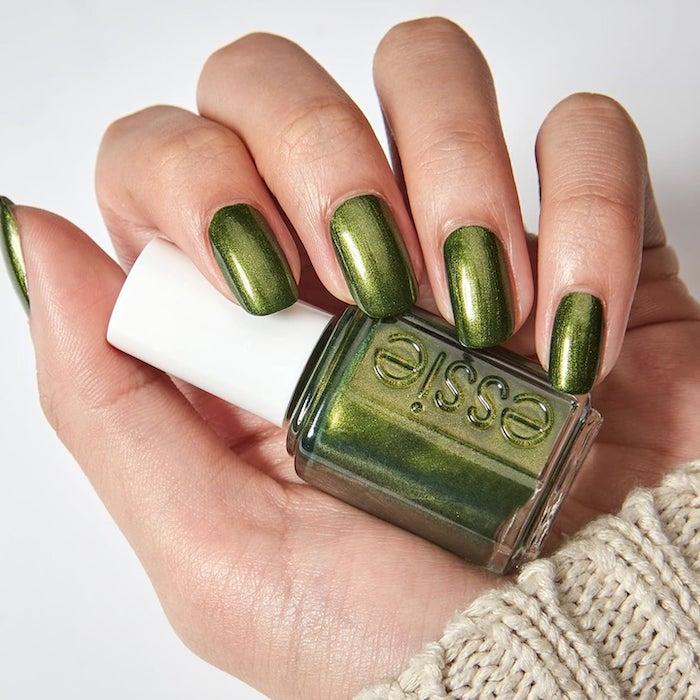 hand holding, nail polish bottle, metallic green, nail polish, short squoval nails, white background, pretty nail colors