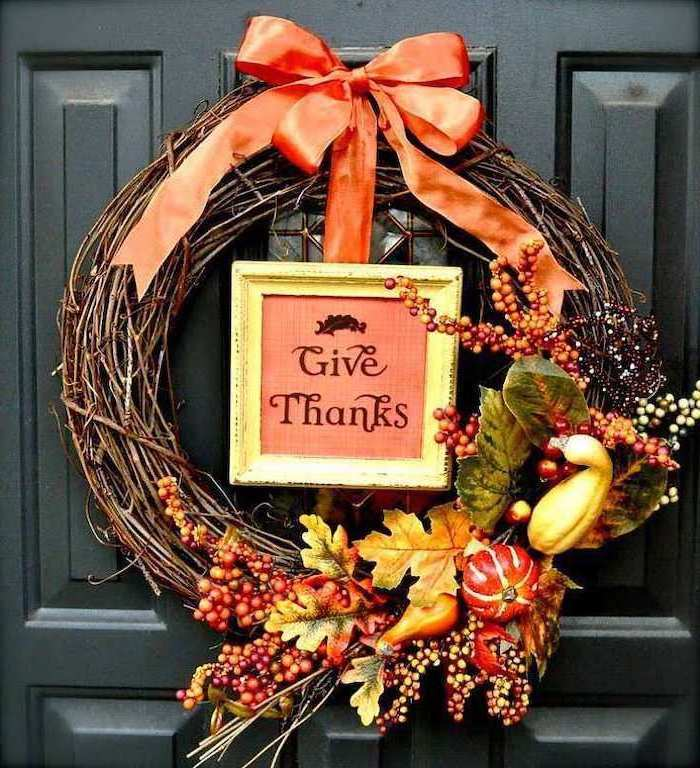 wooden wreath, with faux leaves and fruits, thanksgiving home decorations, black door, orange ribbon