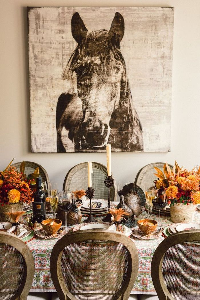 happy thanksgiving sign, wooden chairs, horse painting, flower bouquets, plate settings, turkey figurines, on the table