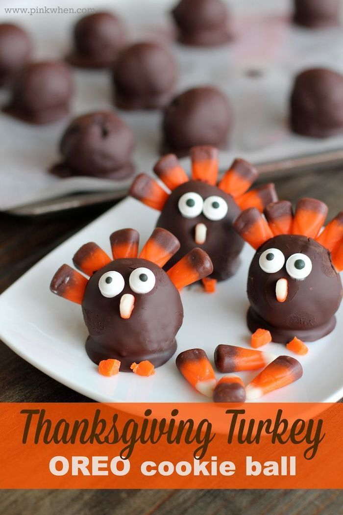 turkey shaped, oreo cookie balls, with candy corn, thanksgiving desserts ideas, white plate, wooden table