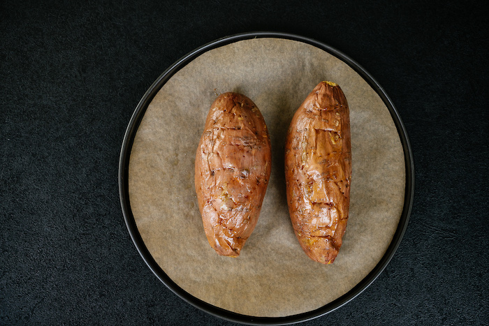 two baked sweet potatoes, easy dinner recipes, on sheet pan, covered with baking paper, on black table