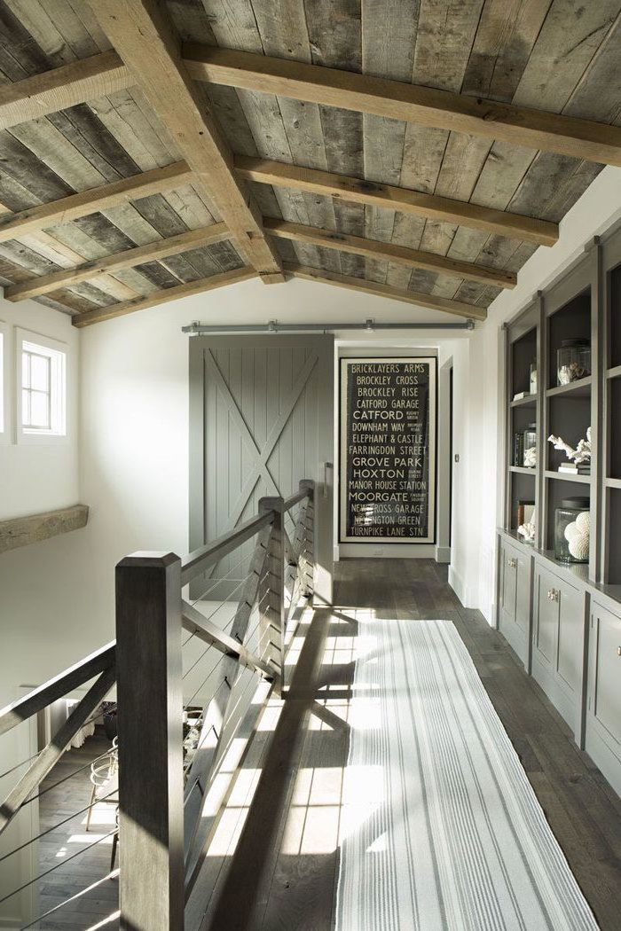 wooden ceiling, metal railing, barn door, vaulted ceiling lighting, grey cupboard and shelving