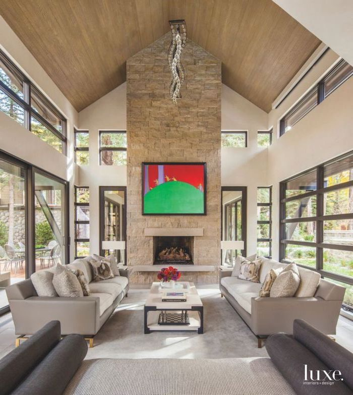 stone fireplace wall, grey sofas, tall windows, vaulted ceiling kitchen, wooden ceiling, white coffee table