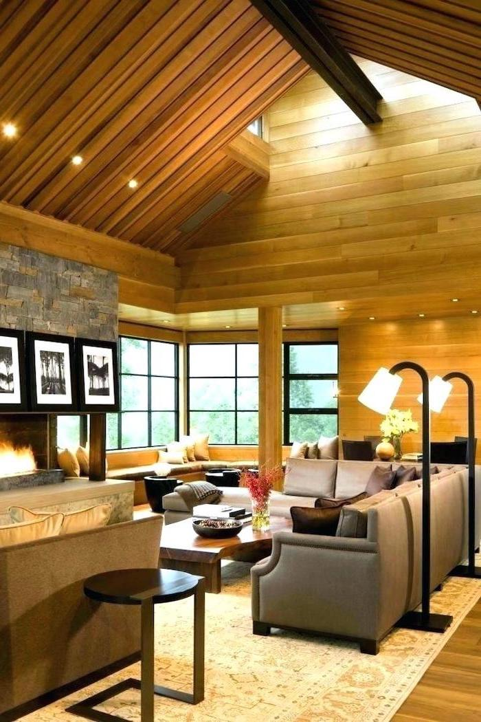 wooden walls and ceiling, grey corner sofa, vaulted ceiling kitchen, stone fireplace, wooden floor, white carpet