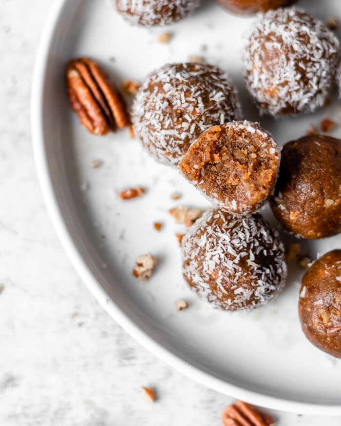 marble countertop, healthy energy balls, covered with coconut flakes, walnuts in white palte