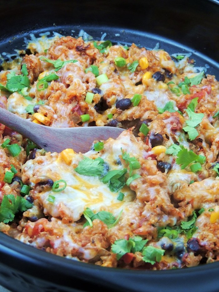 black skillet, chicken enchilada, with quinoa and tomatoes, black beans and corn, easy weeknight dinners, stirred with wooden spoon