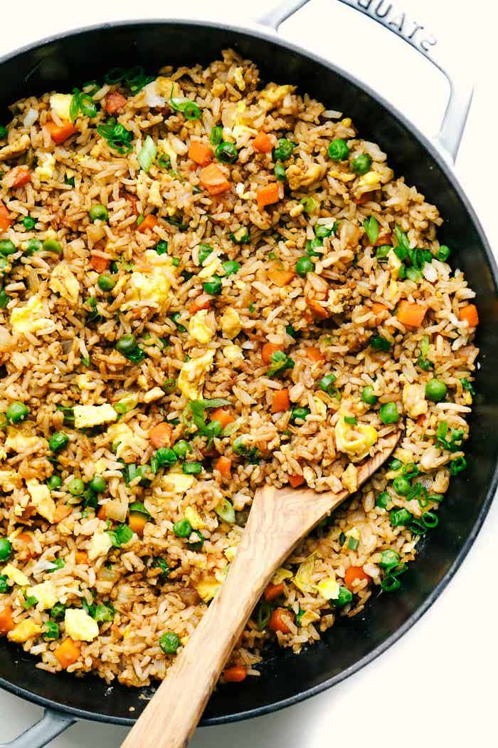 rice with vegetables, cooked in a skillet, easy weeknight meals, wooden spoon on the side, white table