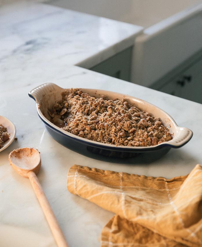 black white casserole, apple crumble, easy thanksgiving desserts, marble countertop, wooden spatula, orange cloth