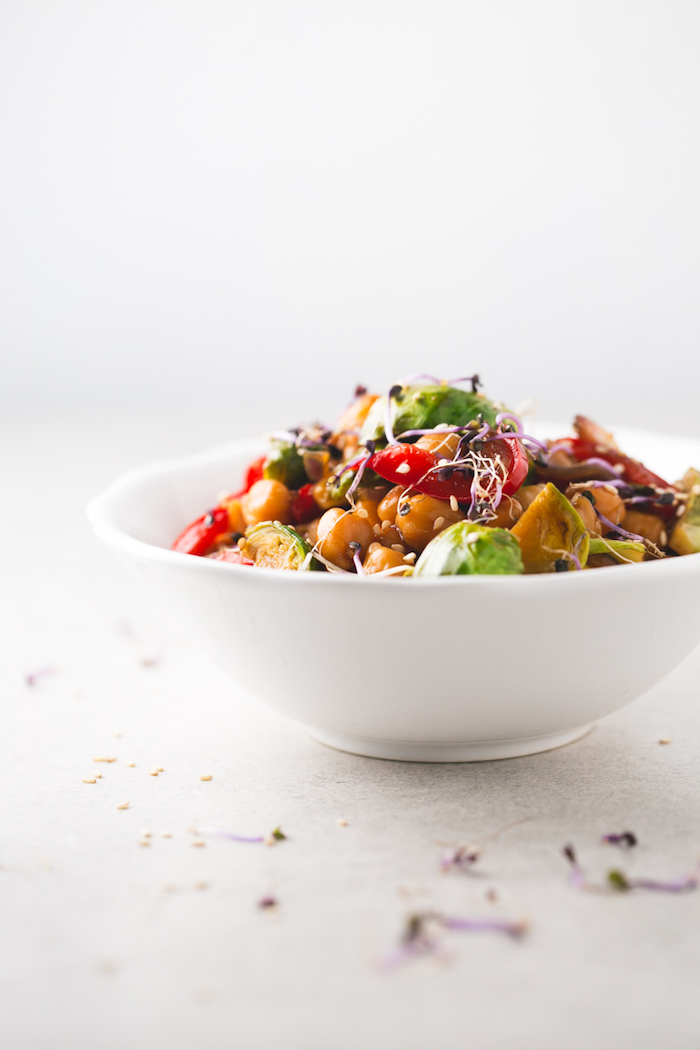 white table, healthy dinner ideas, chickpeas and vegetables stir fry, in white ceramic bowl, with sesame seeds
