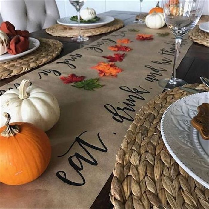 table runner, pumpkins and fall leaves, arranged on it, happy thanksgiving sign, wine glasses, plate settings
