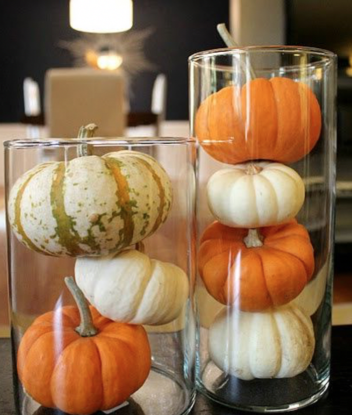 small pumpkins, arranged in tall, glass vases, happy thanksgiving sign, blurred background