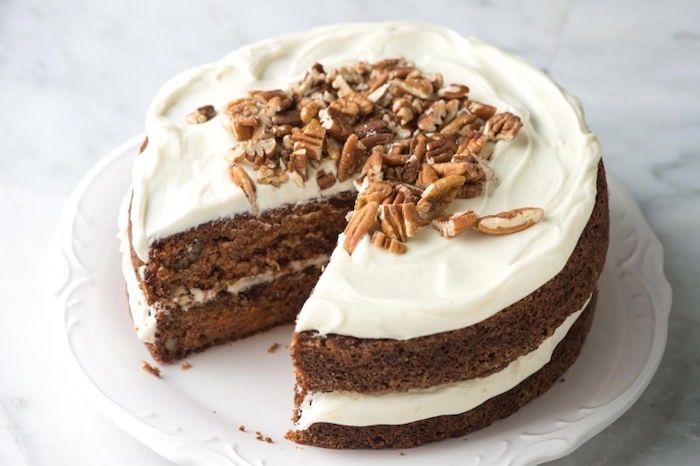 carrot cake, thanksgiving desserts ideas, white frosting, crushed walnuts, white plate, marble countertop