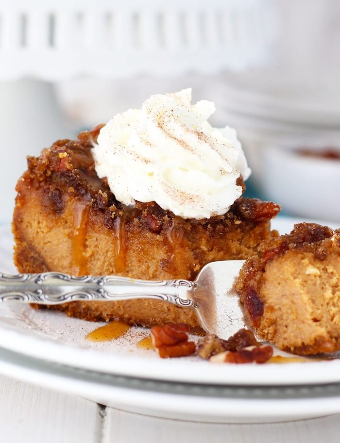 silver fork, white plate, thanksgiving dessert recipes, slice of cake, pecan cheesecake, caramel drizzle, cream on top