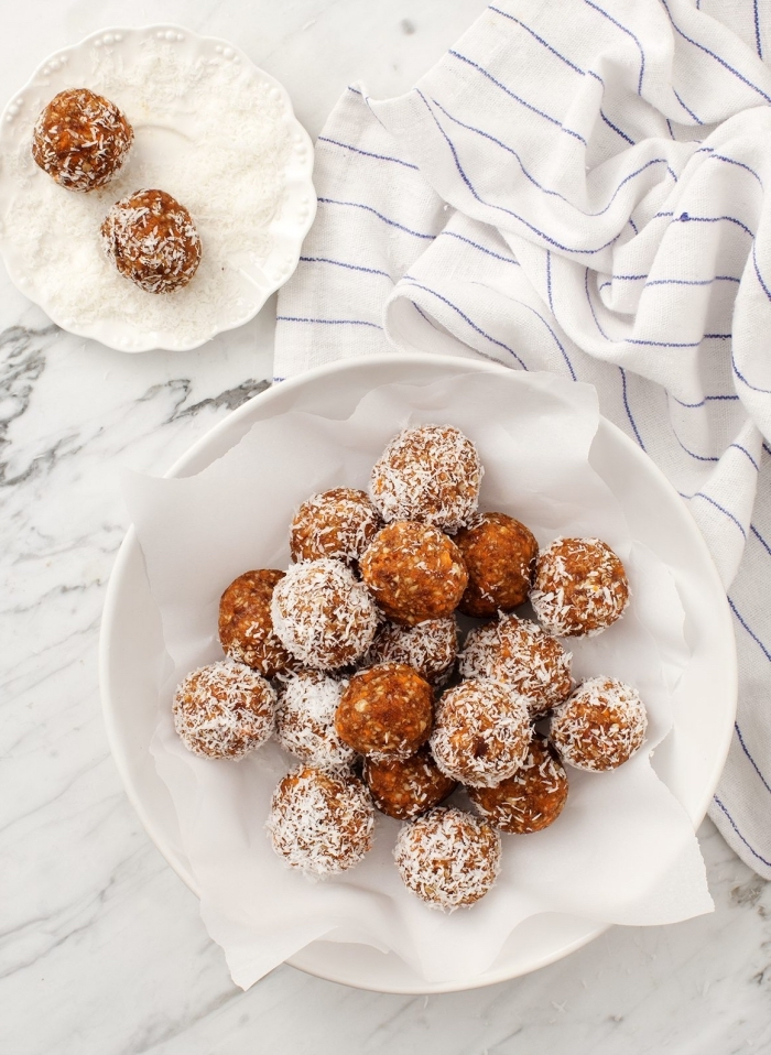 energy balls recipe, covered with coconut flakes, in white plates, white cloth, marble countertop