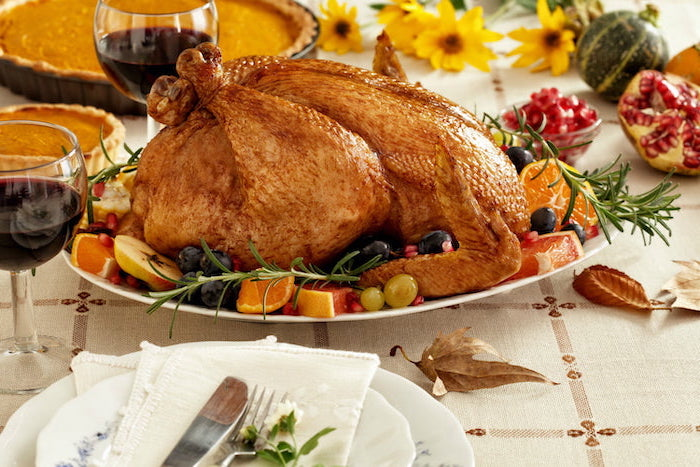 fresh rosemary, grapes and apples, orange slices, on the side, how to make a turkey for thanksgiving, white plates
