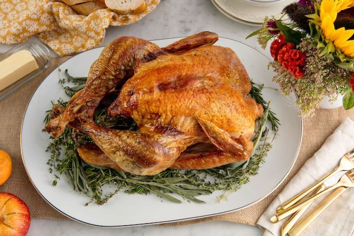 roasted turkey, fresh herbs, white plate, flower bouquet, how to make a turkey for thanksgiving