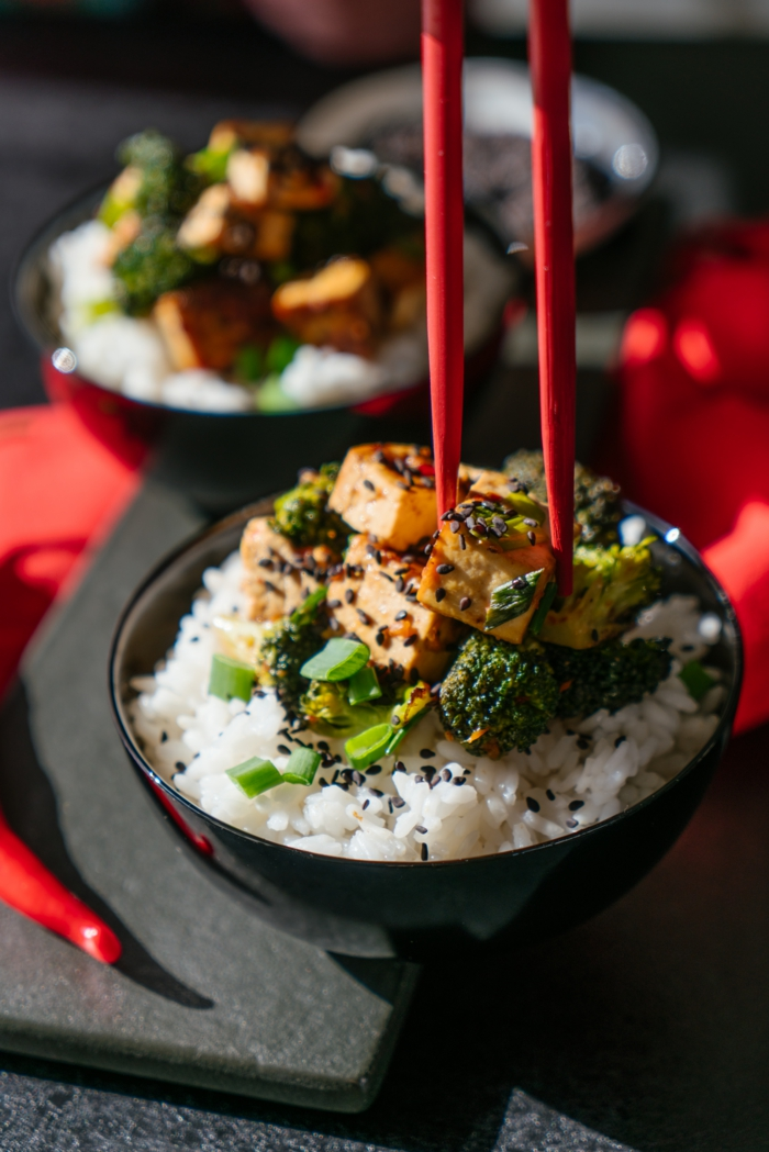 tofu and broccoli on white rice, garnished with black sesame seeds, asian tofu recipe, black bowl and red chopsticks