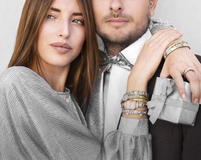 woman hugging a man, holding a silver gift box, christmas gift ideas, wearing lots of bracelets