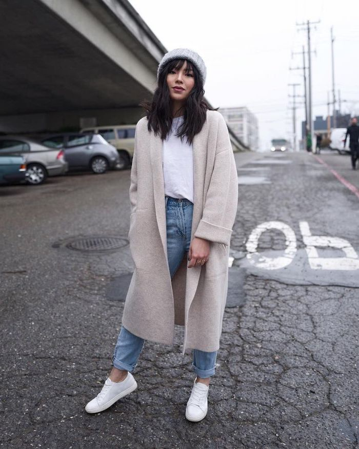 woman in the middle of the street, wearing long coat and jeans, medium length hairstyles with bangs, white sneakers