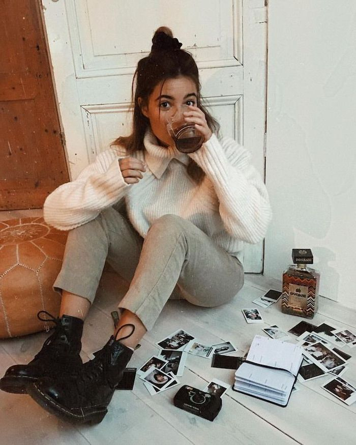 woman sitting on the floor, medium length hairstyles with bangs, wearing white sweater and grey pants, dr martens boots