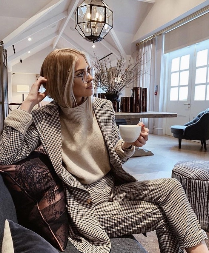 woman sitting on a sofa, wearing a black and white suit, white sweater, short to mid length hairstyles, blonde hair