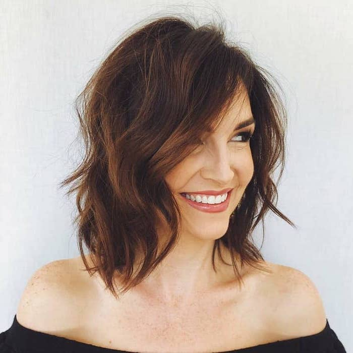 woman smiling, short to mid length hairstyles, wearing off the shoulder black blouse, brown wavy hair, white background
