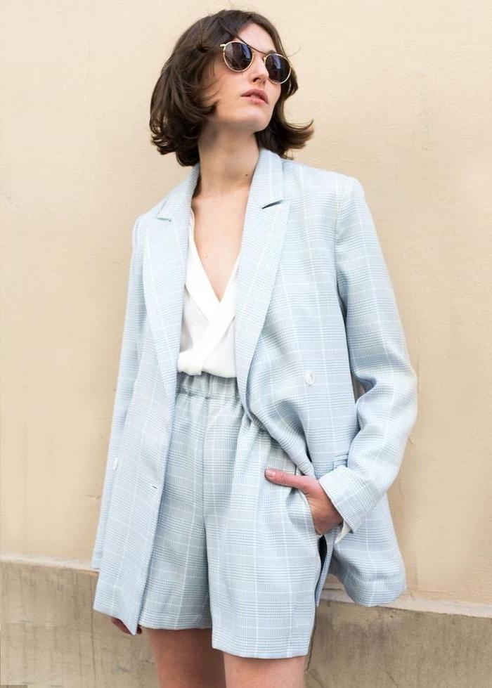 woman leaning on a wall, wearing a blue suit with shorts, white shirt, short to mid length hairstyles, black hair